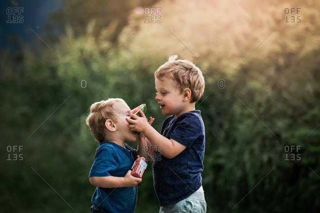 Two little boys feeding each other watermelon