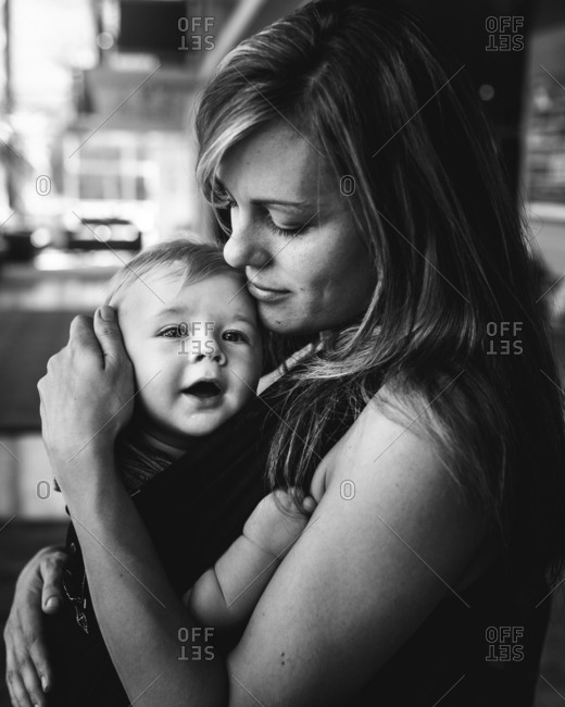 Mother holding baby in carrier in black and white