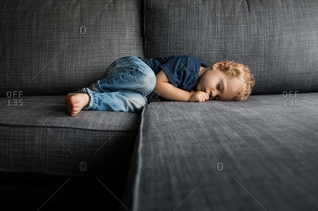 Baby sleeping on gray sofa