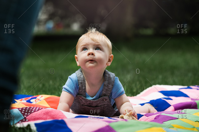 Baby boy on quilt looking up while at a picnic