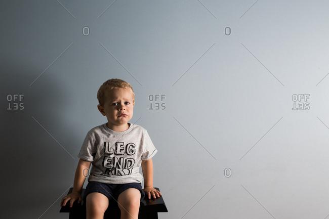 Toddler boy sitting on stool crying