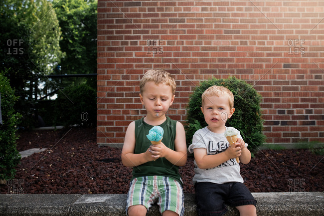 Two little boys eating ice cream cones