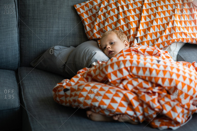 Sick toddler resting on sofa