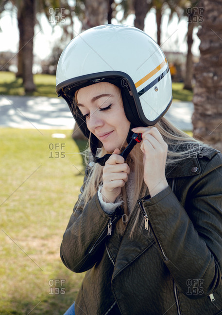 Close-up view of woman adjusting helmet before riding a scooter motorbike