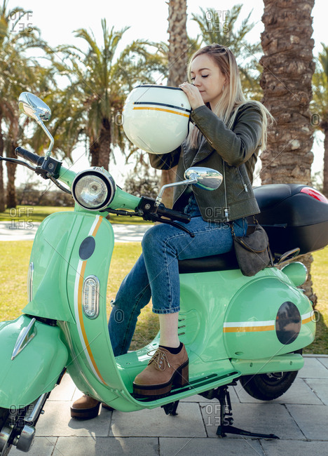 Woman adjusting helmet before riding a scooter motorbike
