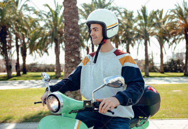 Young handsome man in colored hoody and helmet looking along smiling and sitting on green scooter