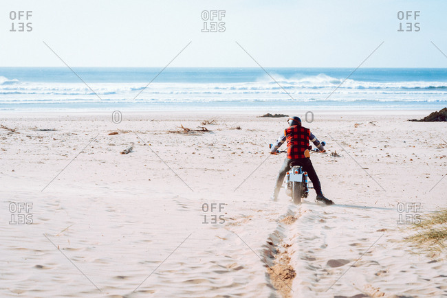 Back view of man sitting on motorcycle while exploring sandy beach with majestic ocean view