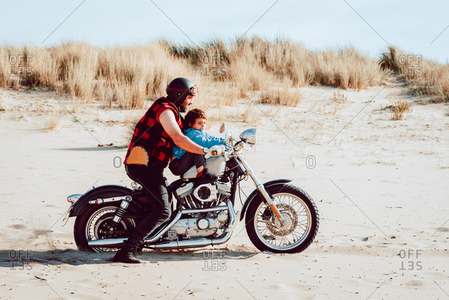 Adult brutal father with son riding motorcycle together on empty sandy beach of ocean