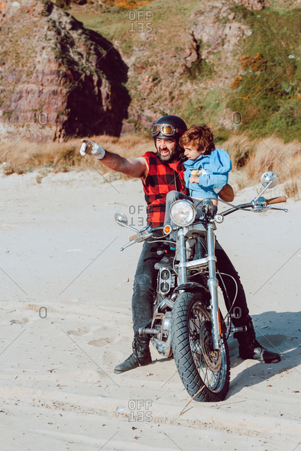 Adult brutal father with son sitting on motorcycle together and pointing on empty sandy beach of ocean