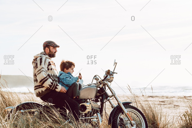 Adult brutal father with son sitting on motorcycle together on empty sandy beach of ocean