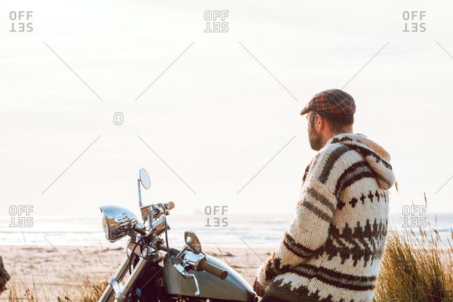 Adult man sitting on motorcycle on empty sandy beach of ocean