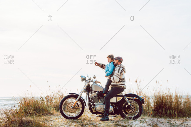 Side view of adult bearded man in sweater and little boy sitting together on motorcycle spending time on ocean shore