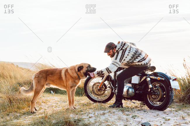 Man in sweater and cap sitting on motorcycle and caressing dog with ocean seashore on background