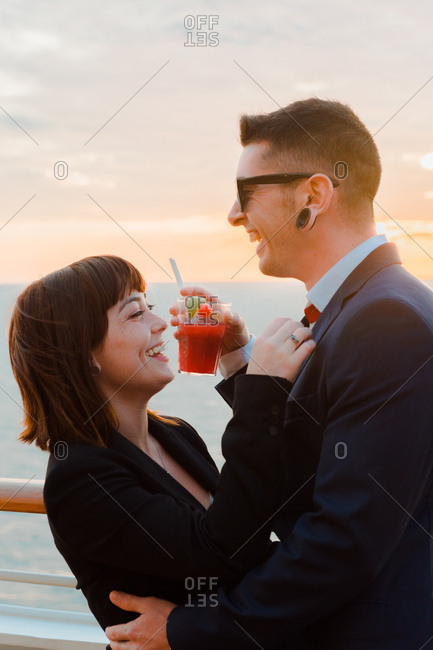 Side view of young attractive couple drinking red beverage with straws from one glass on background of sunset sea