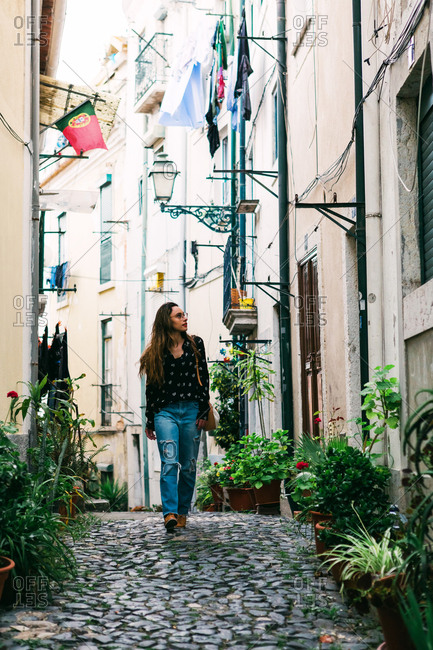 Young casual brunette walking on cobblestone street of old city