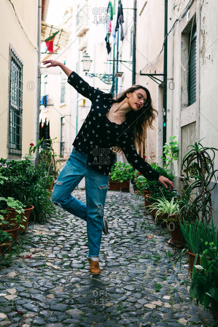 Young casual brunette in glasses standing in graceful pose while dancing on cobblestone street of old city