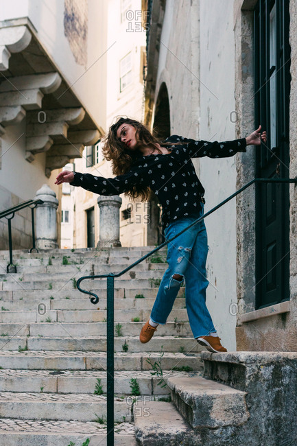 Young slim casual woman stretching and dancing on stairway while dancing gracefully on street of old city