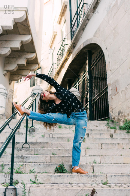 Young slim casual woman stretching on stairway while dancing gracefully on street of old city