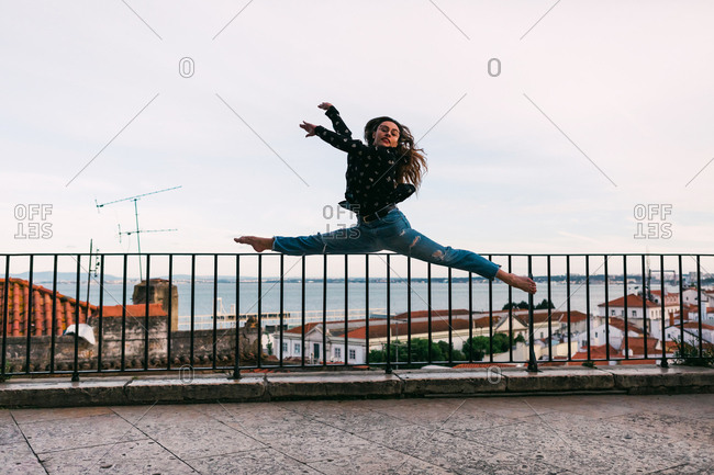 Side view of casual teen woman flying in splits while dancing beautifully on background of coastal city
