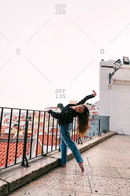 casual teen woman in splits while dancing beautifully on background of coastal city