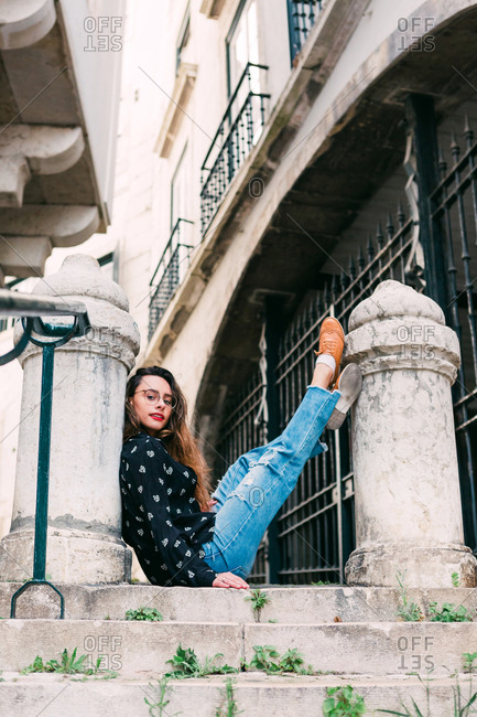 Side view of young casual teen woman sitting on old stairway lifting legs on stone pillar near looking at camera