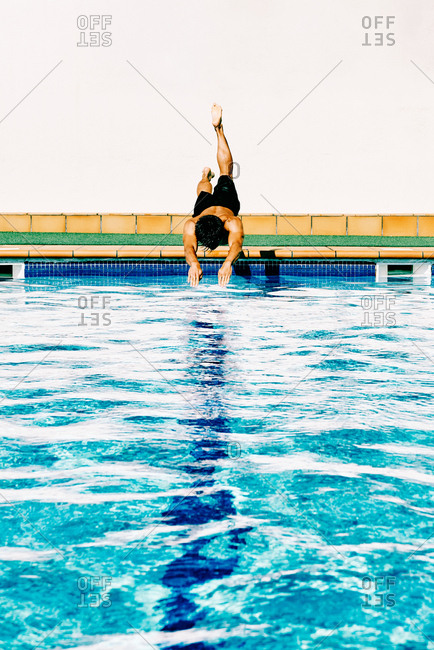 a young man jumping to the pool