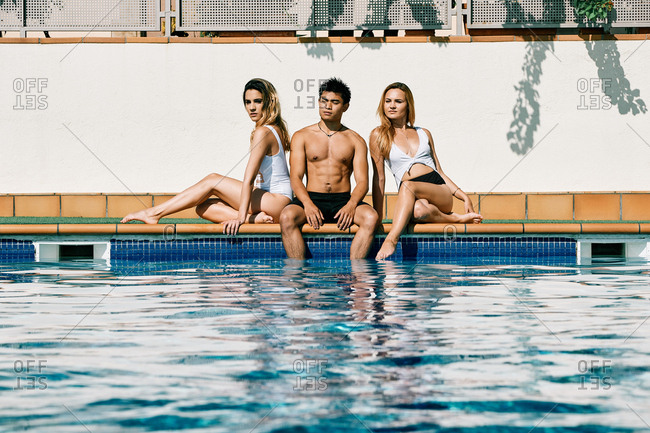 two young women and an asiatic man by the pool