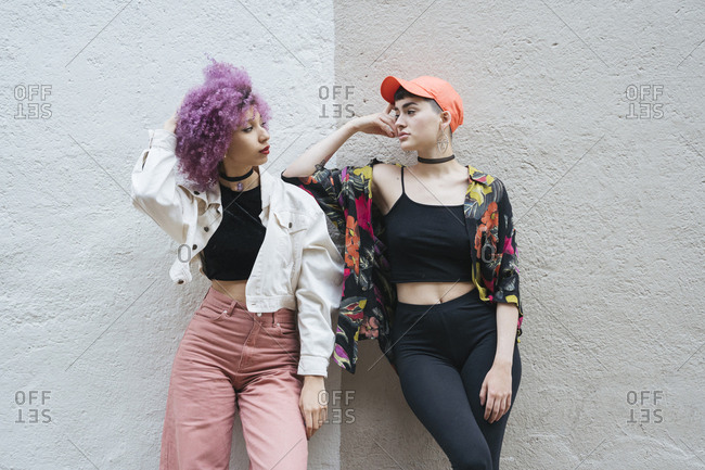 Girlfriends leaning on wall posing side by side together and looking at each other