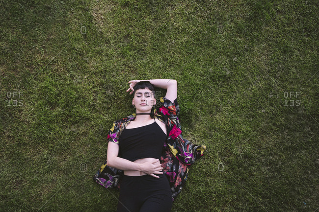 From above young attractive stylish woman in colorful shirt lying on green grass with closed eyes