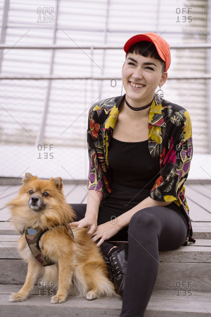 Light brown dog with young cheerful trendy woman in bright clothes sitting on street