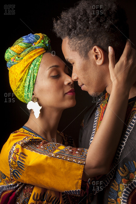 Side view of young attractive African couple in bright ethnic clothes hugging with closed eyes