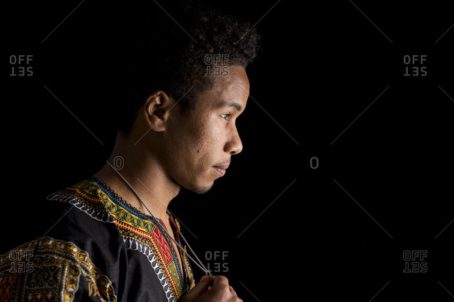 Side view of young African man in ethnic clothing thoughtfully looking away and holding pendant in hands