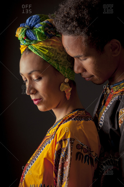 Side view of young attractive African couple in bright ethnic clothes