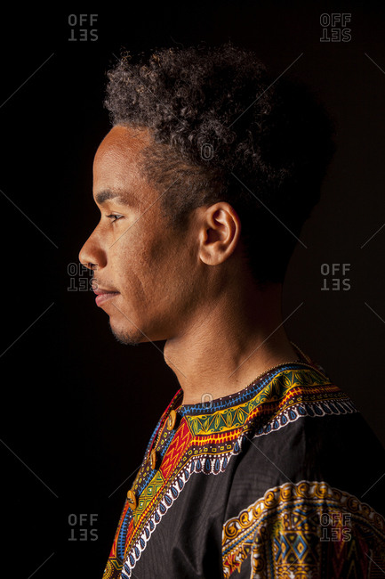 Side view of young African man in ethnic clothing thoughtfully looking away and smiling