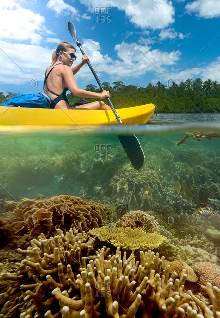 Side view of young female tourist traveling on kayak in tropical lagoon with picturesque bottom