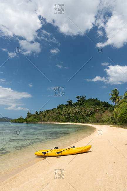 Empty yellow canoe on sandy beach of tropical island on background of jungle and blue sky