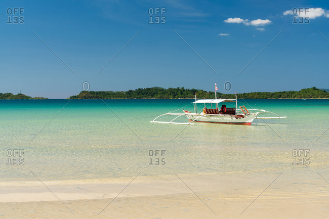 Boat at rest on shallow of sandy seashore in tropical paradise beach
