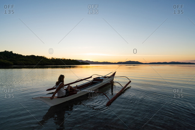 Back view of female traveller resting in boat and looking at picturesque sundown