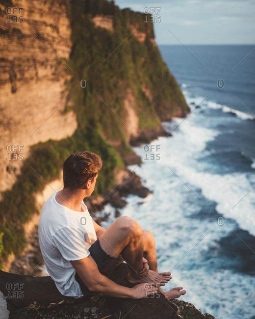 Side view of man sitting alone on cliff at height looking at majestic landscape of ocean waves, Bali
