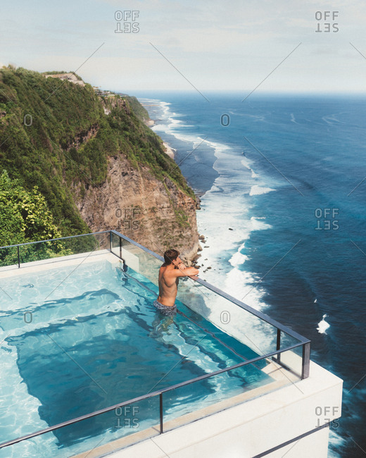From above view of man swimming in resort hotel with amazing view of ocean and cliffs on background, Bali