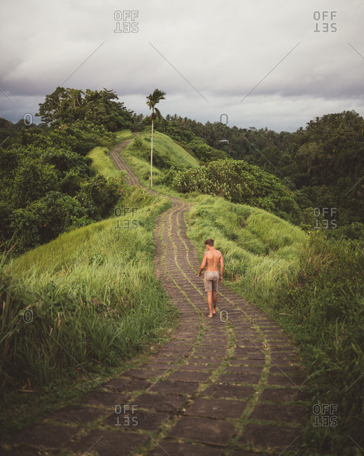 Back view of shirtless man walking on stone paved road on edge of green tropical mountain in windy day, Bali