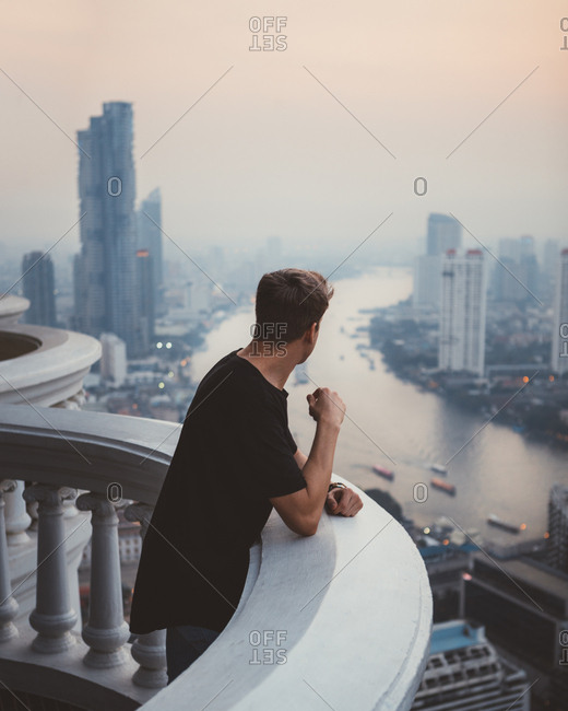 Man on balcony viewing Bangkok in haze