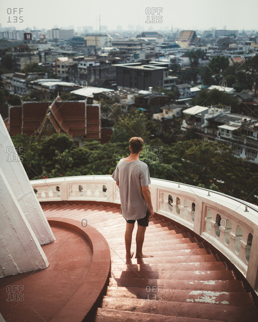 Back view of barefoot traveler standing on stairway high above city observing view of Bangkok in sunlight, Thailand