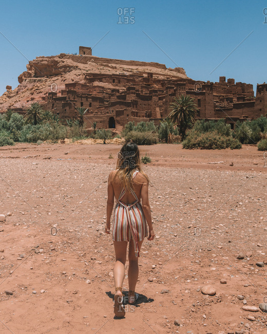 Back view of stylish woman walking on dry terrain of Moroccan desert against aged stone city in rock