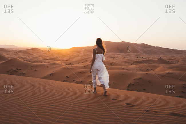 Back view of barefoot woman in white summer dress walking on sandy dune of endless desert in sunset, Morocco