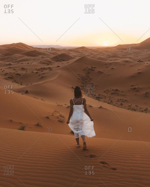 Back view of barefoot women in white summer dress walking on sandy dune of endless desert in sunset, Morocco