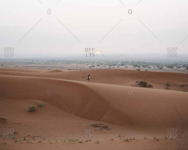 Back view of barefoot woman in summer dress walking on sandy dune of endless desert in sunset, Morocco