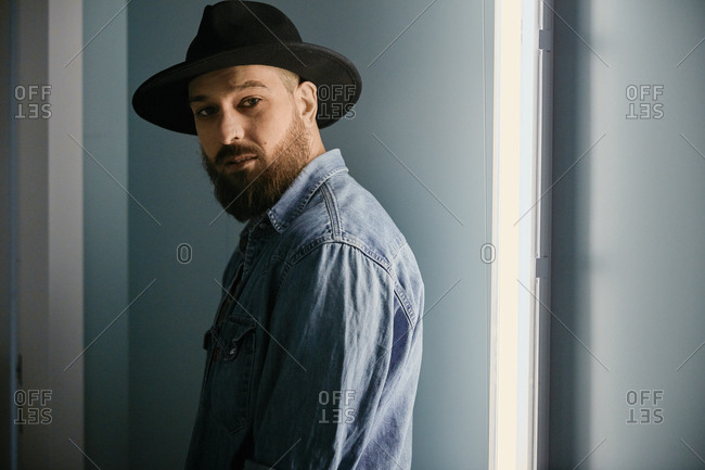 Young bearded handsome man in hat and denim shirt looking at camera in dark room