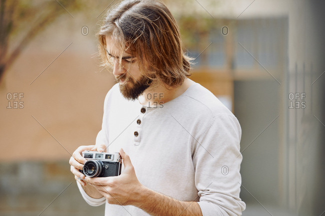 Young bearded handsome man in casual clothes taking photo in street
