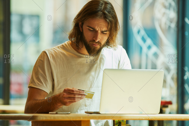 Young bearded handsome man sitting in outside cafe and working holding notebook on table